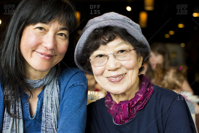 Older Japanese mother and daughter smiling in restaurant