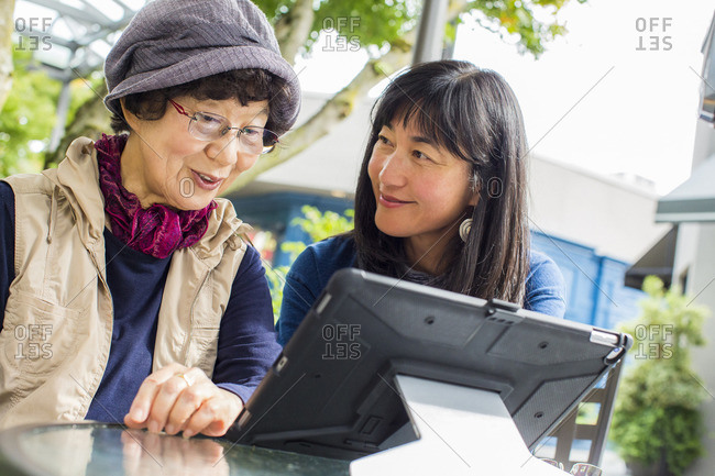 Older Japanese mother and daughter using digital tablet