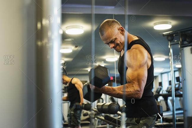 Hispanic man weightlifting in gymnasium