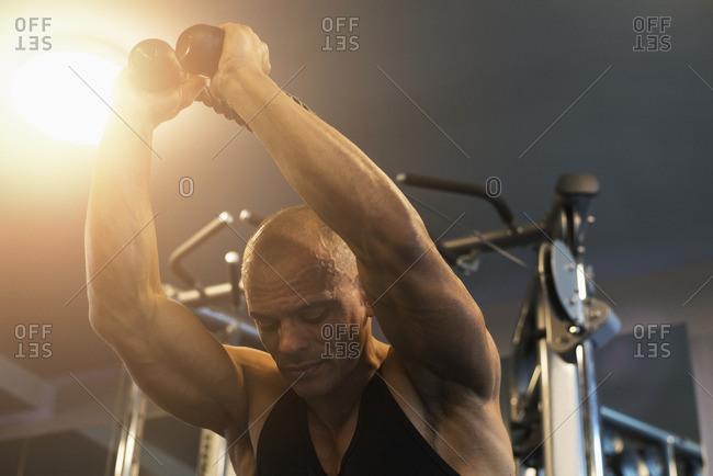 Hispanic man pulling rope gymnasium