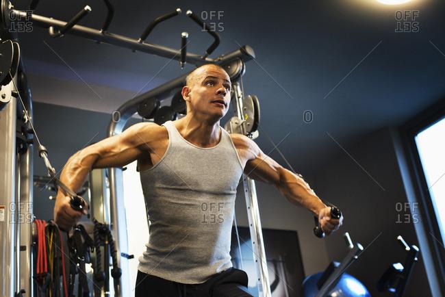 Hispanic man pulling handles in gymnasium