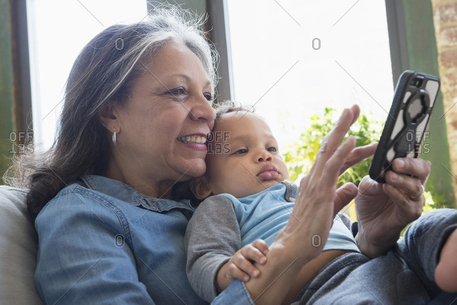 Hispanic grandmother holding grandson and texting on cell phone