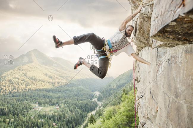 Caucasian man hanging from rock while climbing