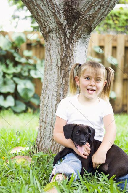 Caucasian girl leaning on tree hugging dog