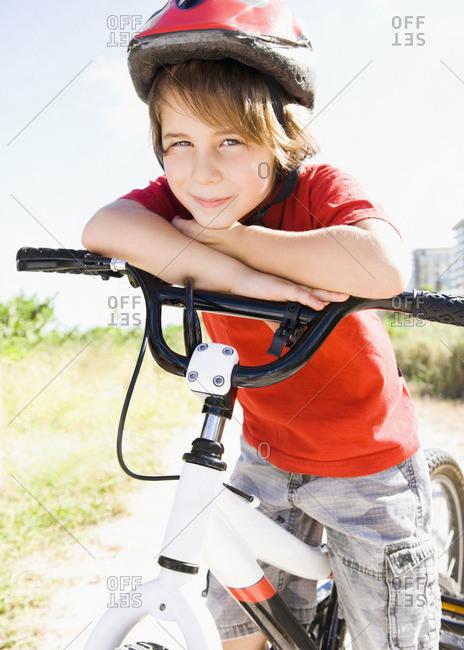 Caucasian boy leaning on bicycle handlebar