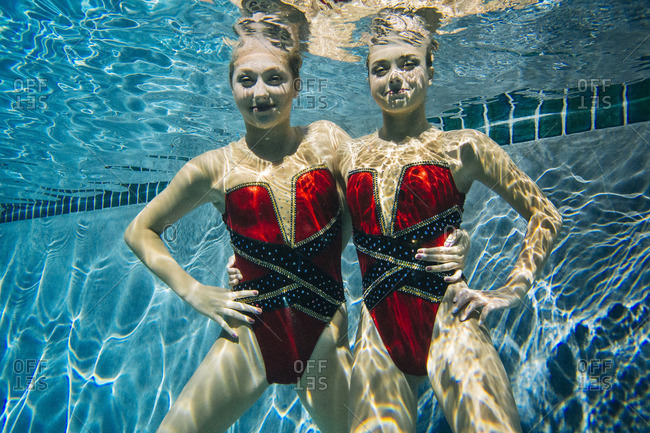 Portrait of synchronized swimmers smiling underwater