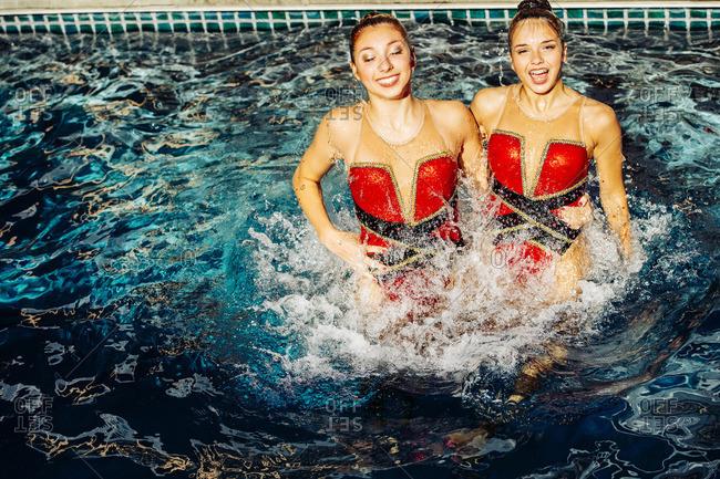 Caucasian synchronized swimmers splashing in swimming pool