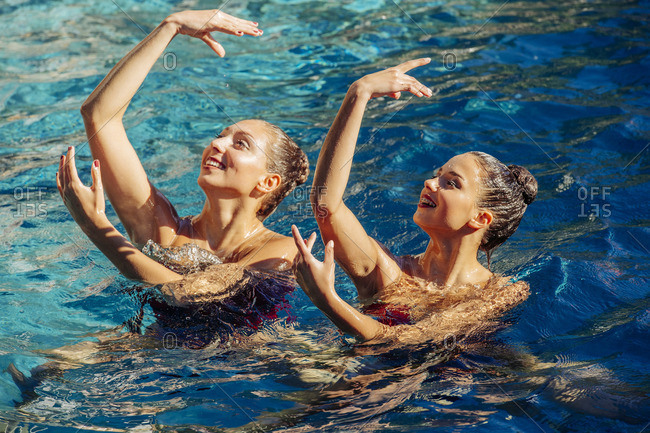 Caucasian synchronized swimmers with arms raised