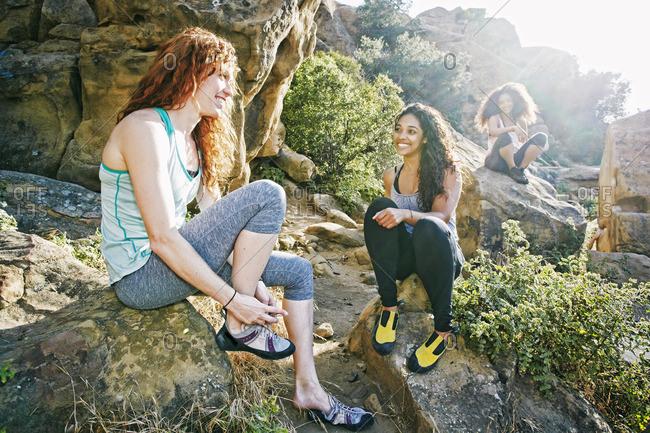 Smiling women sitting on rocks preparing for rock climbing