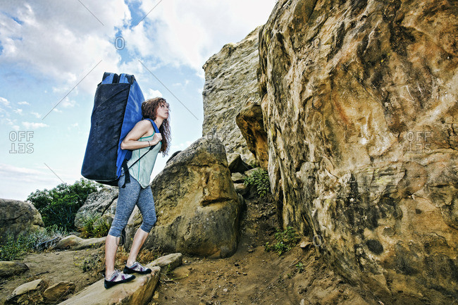 Caucasian woman carrying large backpack near rock formation