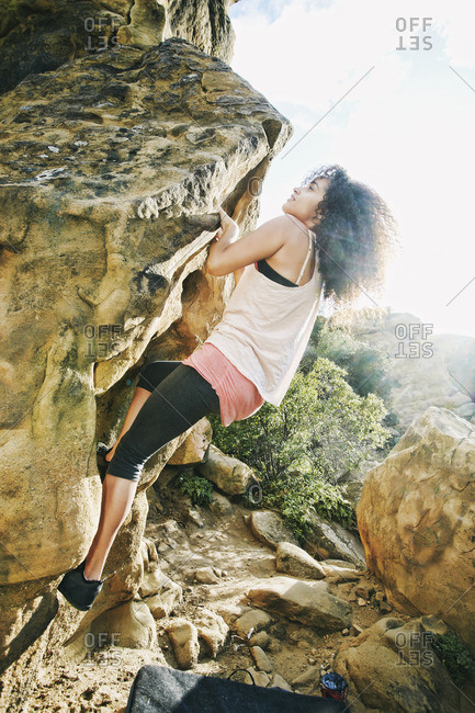 Hispanic woman rock climbing