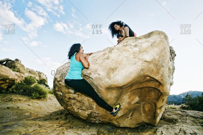 Women climbing on boulder