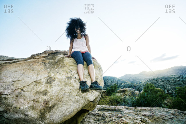 Hispanic woman sitting on boulder in wind