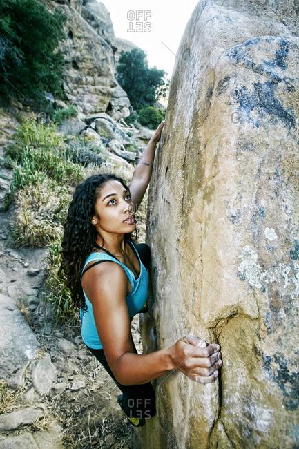 Mixed Race woman rock climbing