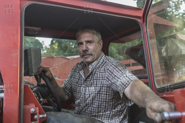 Caucasian man holding door of tractor