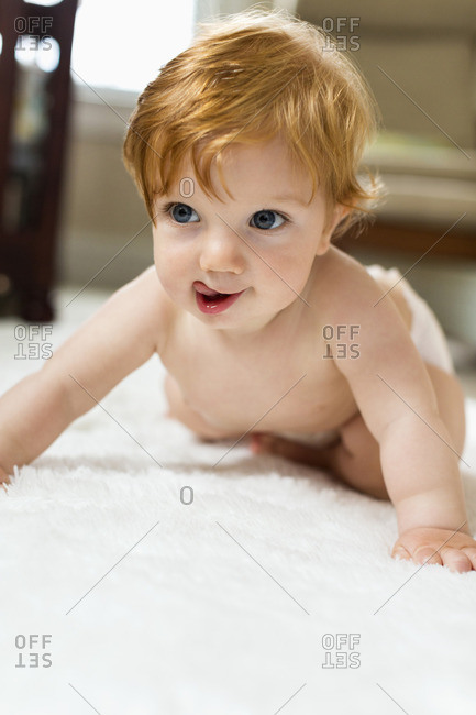 Caucasian baby boy crawling on carpet