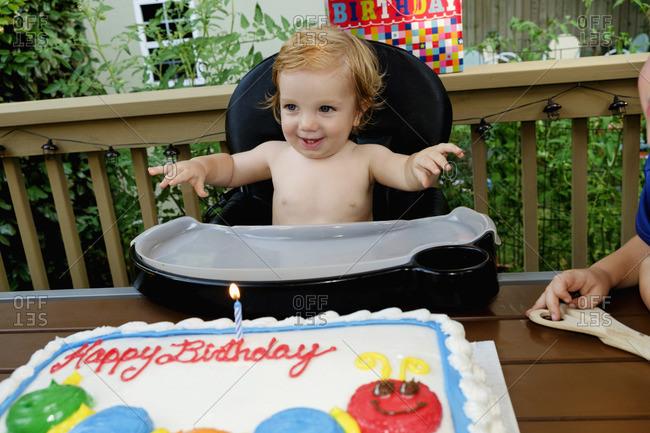 Caucasian baby boy in high chair near birthday cake