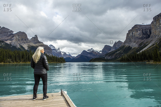 Caucasian woman standing at the end of dock on mountain lake