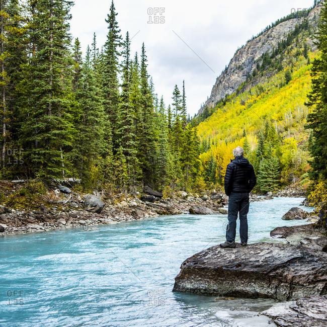 Caucasian man standing on rock near mountain river