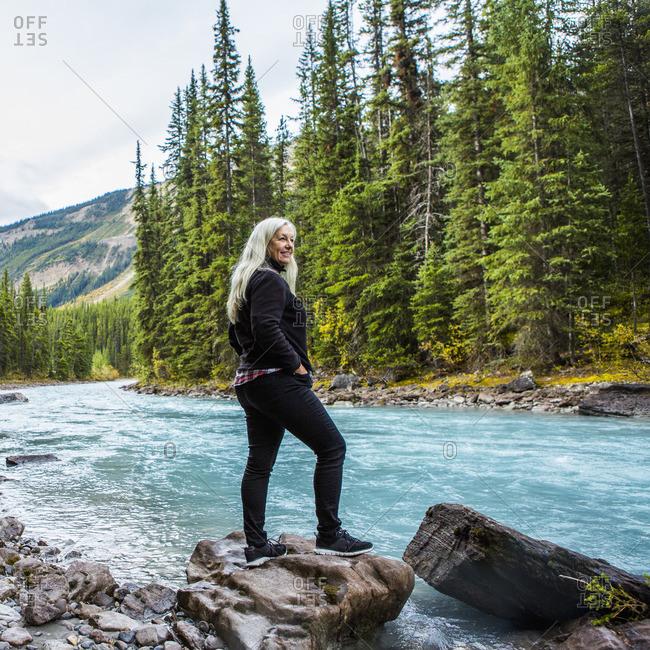 Caucasian woman standing on rock near mountain river