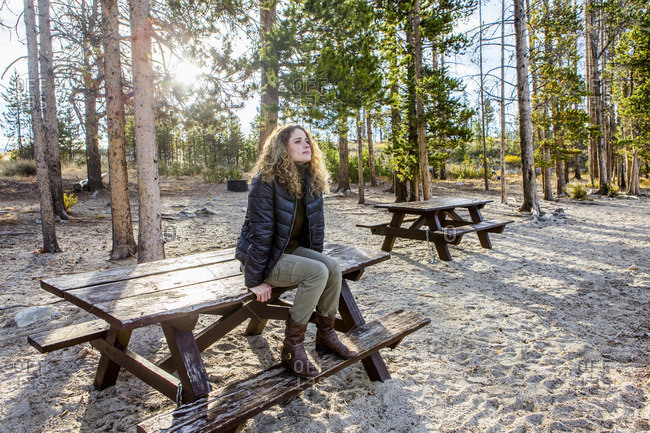 Caucasian woman sitting on picnic table