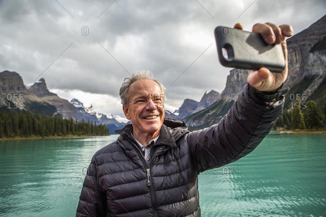 Caucasian man posing for cell phone selfie near mountain lake