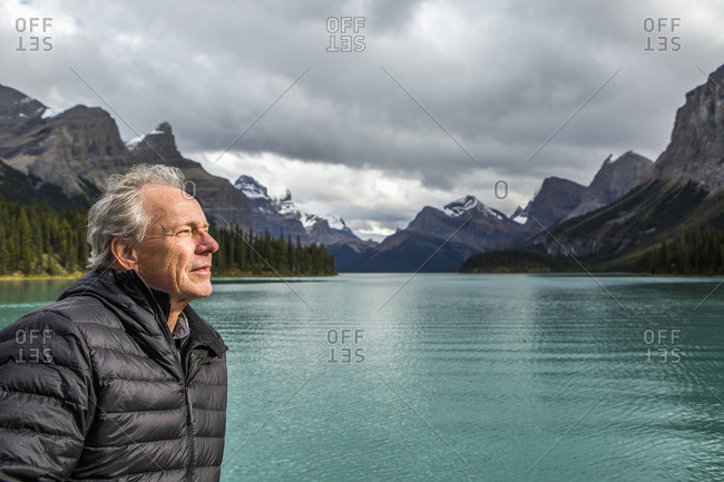 Caucasian man standing near mountain lake
