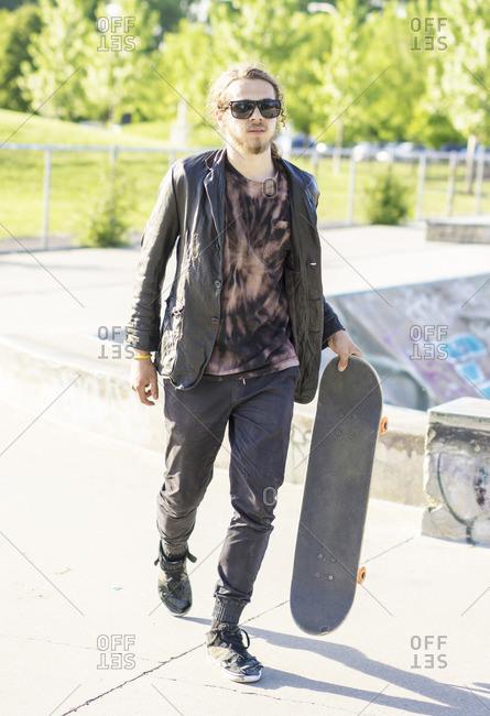 Caucasian man with beard carrying skateboard
