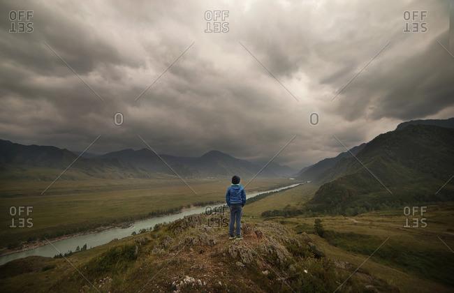 Caucasian boy standing near river in cloudy landscape