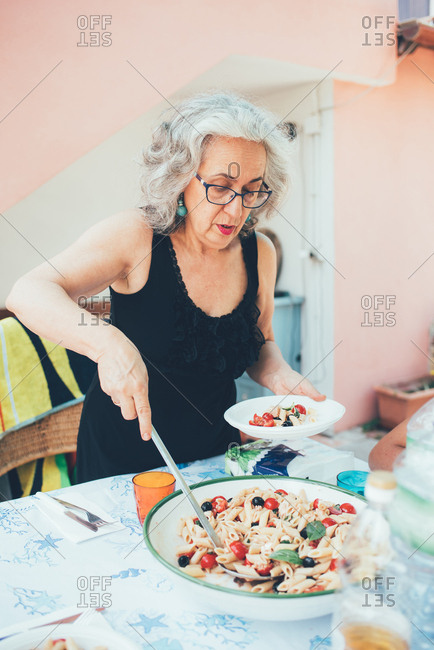 Woman serving pasta from serving dish