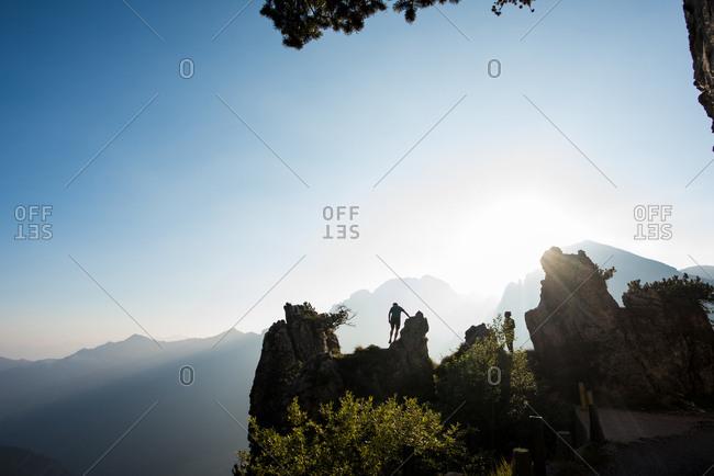 Silhouettes of distant couple on mountain peak, Passo Maniva, Italy
