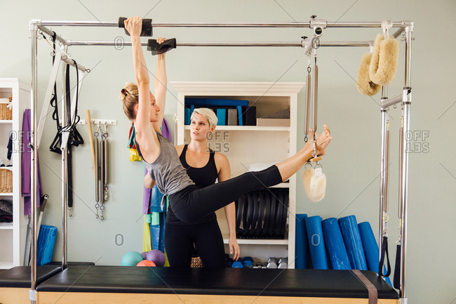 Side view of woman hanging from pilates reformer