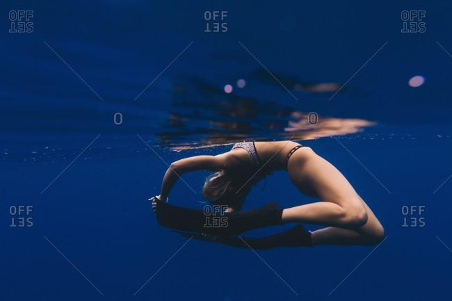Woman free-diver doing acrobatics in sea
