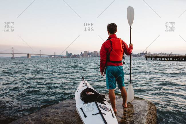 Man with kayak and oar, looking out to sea, San Francisco, California, USA
