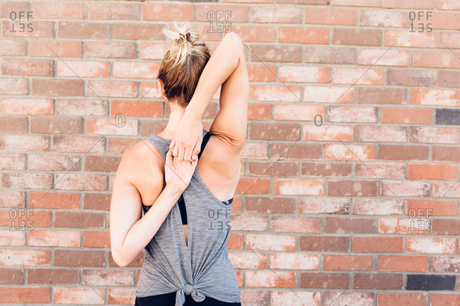 Rear view of woman, arms behind back stretching