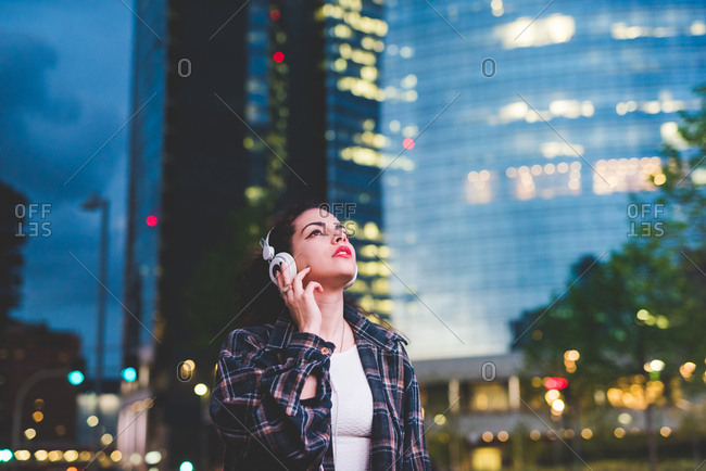 Woman wearing headphones in the city looking up, Milan Italy