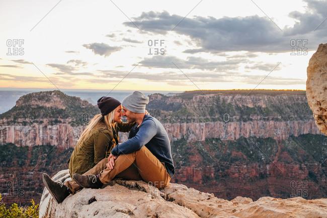 Couple sitting nuzzling on edge of Grand Canyon, Arizona, USA