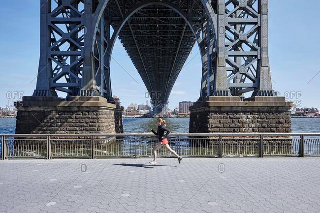 Young woman exercising outdoors, running underneath Williamsburg Bridge, New York City, USA
