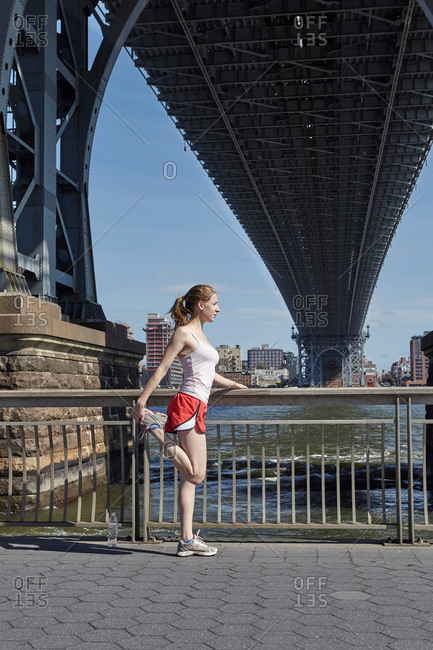 Young woman exercising outdoors, stretching, underneath Williamsburg Bridge, New York City, USA