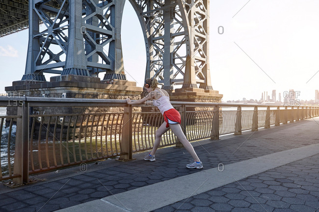 Young woman exercising outdoors, stretching underneath Williamsburg Bridge, New York City, USA