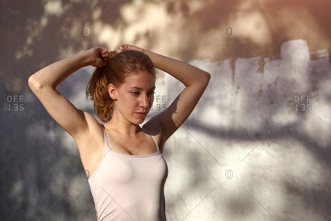 Woman tying up ponytail