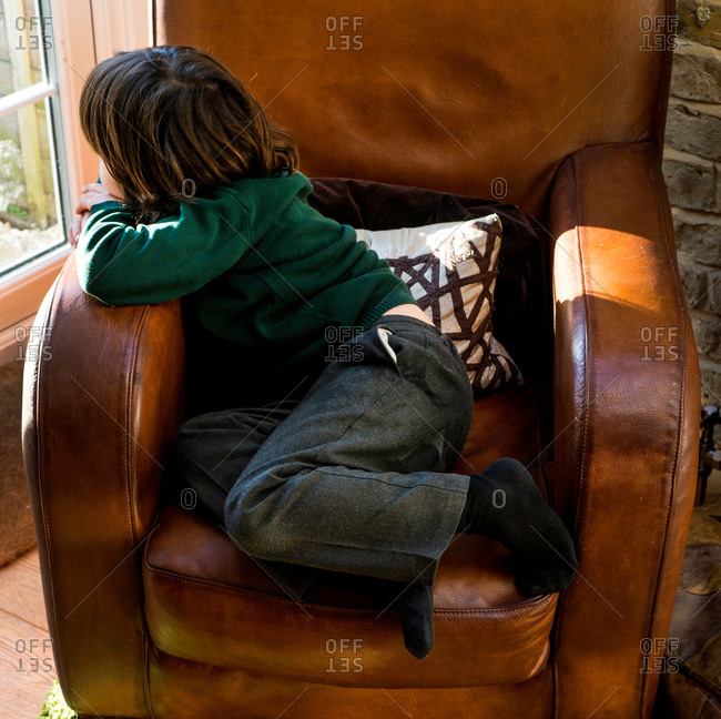 Boy relaxing on arm chair after school