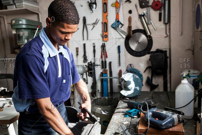 Young man using pliers in repair workshop