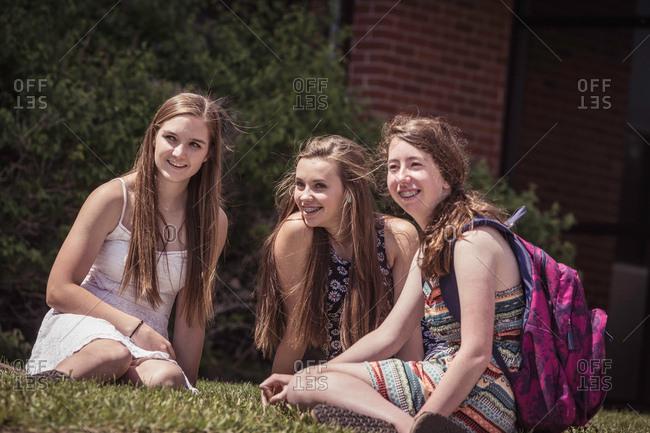 Female high school students sitting on grass outside high school
