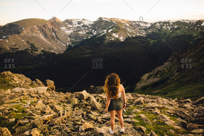 Rear view of woman on rocky outcrop looking at view, Rocky Mountain National Park, Colorado, USA