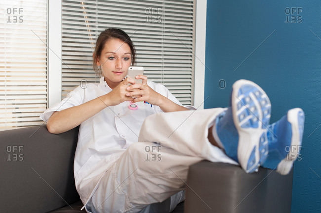 Nurse sitting in chair with legs up using smartphone