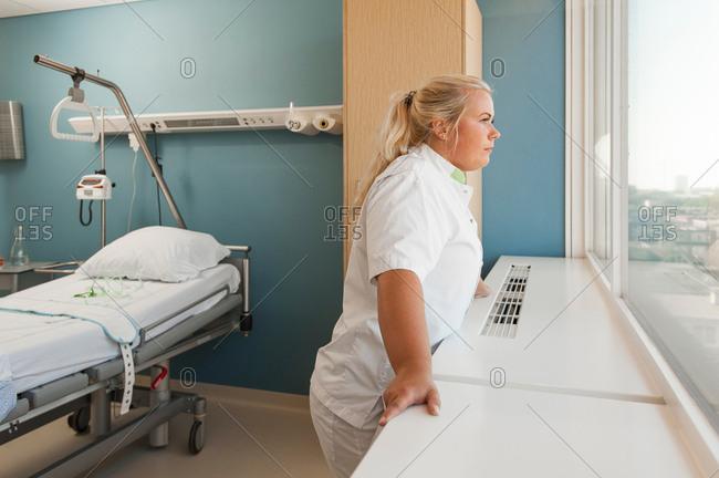 Nurse on hospital ward looking out of window