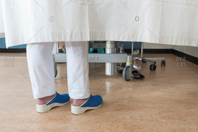 Feet of nurse behind hospital room privacy curtain