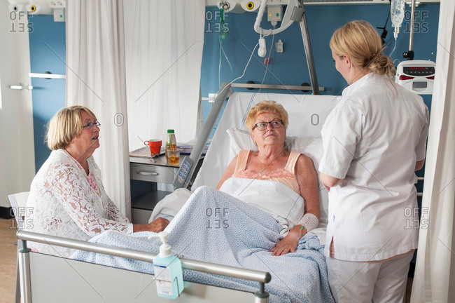 Nurse and visitor tending to patient in hospital bed