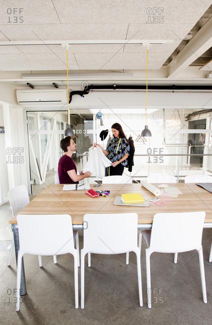 Fashion designer showing colleague complete garment